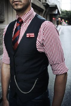 red gingham shirt, red and navy striped tie, skull lapel pin, navy waistcoat