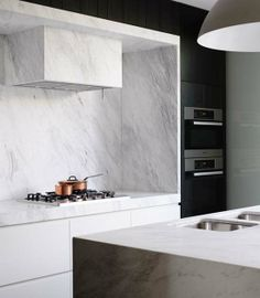 A contemporary kitchen with black cabinets, marble and copper details designed by Mim Design. Photo by Derek Swalwell   My Paradissi