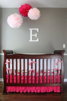 A pop of pink! Dark gray walls with a brown crib and white bedding and a bright pink crib skirt.