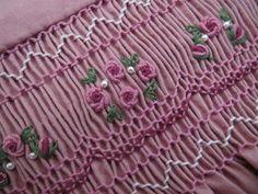 Este pequeño vestido de verano sin mangas viene de una hermosa 100% algodón tela rosa rosada profundo y es mano smocked en hermosas tonos de luz al oscuro color de rosa y marfil. Lingotes de racimos de color de rosa con hojas verdes entremezclados con pequeñas perlas de Marfil decorar el fruncido en la parte delantera. La blusa se alinea y todos los bordes están acabados con una fina costura francesa. El dobladillo se cose con una puntada escondida y este vestidito todo se hace con la máxima…