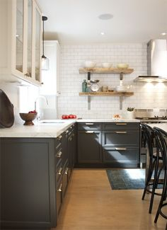 white upper cabinets, dark grey bottom cabinets, brass hardware, white subway tile, marble countertops and rustic floating shelves.
