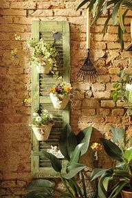 Hanging Flower pots on a shutter.Great use of angles and odd numbers in this design! Hangapot hangers work great for this project. www.hangapot.com