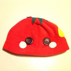 A strawberry beanie/plushy hat! It's made out of soft, kind of stretchy polar fleece! The leaves, pink blush marks and yellow seeds are made out of felt, and securely hot glued on. The eyes are black buttons, and are also securely affixed with hot glue.    The hat would fit on a head with an appr...