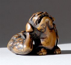 "WOOD NETSUKE Early 19th Century In the form of a shishi seated while scratching his ear. Signed ""Tomochika""."