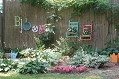 25 Ideas for Decorating your Garden Fence -- Use a variety of bright colored recycled objects and furniture to attach to a fence.