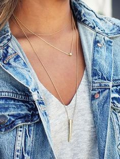 Thin gold necklaces paired with a grey v-neck tee and a denim jacket.
