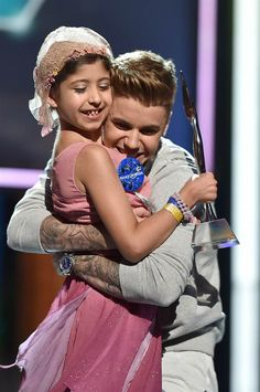 Make-A-Wish recipient Grace Kesablak and Justin Bieber speak onstage at the 2014 Young Hollywood Awards at the Wiltern Theater in Los Angeles, California, on July 27, 2014