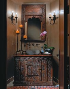 Bathroom altar: Carved wood mirror and vanity, candles, orchid, etc. exudes exotic flare and care.