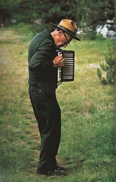 old man playing accordion in the woods.