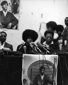 Joan Kelly, spokesman for the Black Panthers, speaks about the December 8th shootout at the Black Panther headquarters on Central Ave. at a press conference held at a vacant lot in Watts, December 11, 1969. Guy Crowder Collection. Tom & Ethel Bradley Center Photographs.