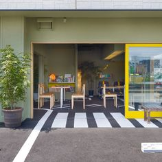 The asphalt surface of a car park extends inside this cafe in Shizuoka, Japan, by Japanese architects Suppose Design Office.