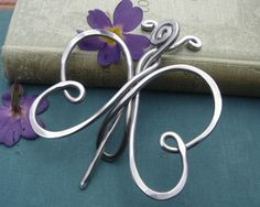 We designed, hammered and twisted 9 gauge aluminum wire to make this lovely butterfly shawl pin or sweater brooch. Aluminum makes it much lighter than it appears. Really! We smoothed all the edges so that it will not catch on your shawl. This pin would work best on a knit or crocheted open weave type garment and is not intended for tightly woven cloth fabric.  The butterfly measures about 3 1/2 - 3 3/4 (8.9 - 9.5cm) from the top of its antennas to the bottom of its wings. It measures about 2…