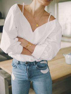 {White top, gold details and denim.}