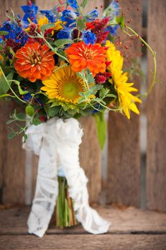 Rustic wildflower bouquet bright yellow, orange & blue Photograph by Sarah Cocina Photography http://www.storyboardwedding.com/private-lake-champlain-cottage-wedding-with-country-flair-bright-hues/