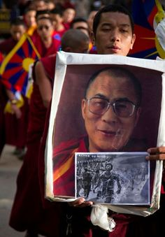 An exiled Tibetan Buddhist monk carries a portrait of the Dalai Lama along with a picture of Jamphel Yeshi during a candle lit vigil in Dharmsala