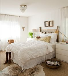 Totally feeling this white and romantic bedroom with accents of gold and a gorgeous chandelier.  Love the raw hide rug too.