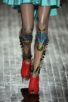 leg jewelry. I love this, It looks like it belongs on a science fiction warrior. This is literally the coolest thing ever, I love how it is paired with the red shoes and it makes the whole look really extravangent and interesting.