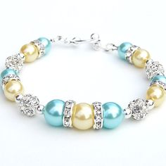 Aqua and Yellow Pearl Rhinestone Bracelet, Bridesmaid Gifts, Summer Jewelry, Beach Wedding, Summer Wedding, Yellow Wedding, Under 30 Aqua and yellow pearls mix with sparkling rhinestones to make this bracelet a lovely summer or bridesmaid accessory. 8 and 10mm glass pearls are strung with rhinestone fireballs. Tiny silver plate seed beads have been used as spacers. The bracelet measures 7.5/19cm and is finished with a silver plate toggle clasp. If you need the length adjusted, just put...