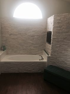 Modern Contemporary Master Bathroom Remodel - White ledger stone surrounds walk in shower bathtub wall Cut out for flat screen tv above the bathtub. Wood floor ceramic tiles.