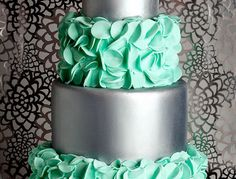 I was asked to create a cake for a local bridal magazine.  They wanted something soft and hard.  So I started with two tiers that I covered in gray fondant.  I used Chefmaster silver spray to achieve the metallic finish.  I did about three coats on each tier.  Then I hand cut turquoise fondant circles and folded them in half to create the petals.  I made the flower out of coral fondant, with a rhinestone center.
