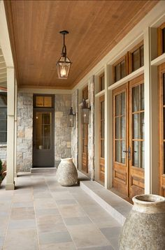Beautiful Lake House - Indiana Limestone porch flooring with stained wood doors, transom windows and ceiling - via Home Bunch Patio Interior, Interior And Exterior, Interior Doors, Stone Interior, Wood French Doors Exterior, Stone Exterior Houses, Ranch Exterior, Exterior Shutters, Exterior Remodel