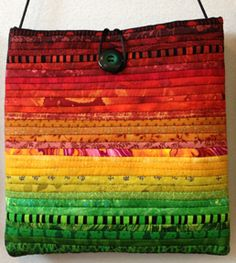 """The Quilts of Ann Brauer: Purses:  Here are just some of fun purses she has available. They all use the thin strip piecing and wonderful colors she is known for. Each is all cotton, quilted through a cotton batting with a cotton back. There is a rayon strap and a button closure. They are about 8 x 8""""."""