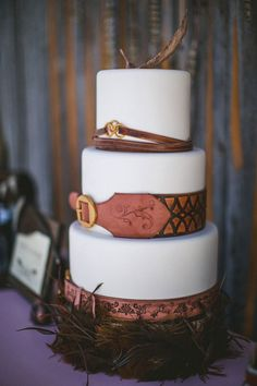 Leather Belts & Feathers Cake {edible belts crafted from modeling chocolate} by Intricate Icings on @The Cake Blog