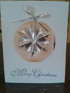 Window cut with circle framelit; inside stamped with stampin up festive flurry, hanging ornament made from festive flurry framelit and silver foil sheet with SU ribbon