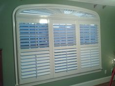 Arched shutter over a triple window of plantation shutters enhances a beautiful architectural window in a home office. The center divider rail in the plantation shutters allows for optimal light control as well as privacy. Southern Accents, Colorful Interiors, Interior, Home, Windows, Light Control, Blinds, Window Treatments, Shutters