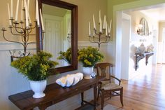 Just past the wooden shelf is a dark accent table and chair contrasting the white wainscoting. Two rustic sconces filled with candles continue that classic styling that is steeped in tradition and contemporary sensibilities.