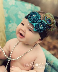 Boutique Couture Rosette Headband Pearls French Netting Peacoc Feathers for Newborns through Adults - $18.95   A pair of Teal handmade satin rosettes are adorned with freshwater pearls in the center and are set upon a black, stretch lace headband. There are 2 Peacock feathers set upon black feathers peeking out from a veiling of black french netting while a string of faux pearl trim hangs delicately around the front. The rosettes and trimmings are hand sewn and securely attached onto this…