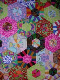 Quilt made with Kaffe Fassett triangles from sewn strips from hexi shape.  Beautiful colors!