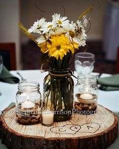 Cedar pieces with mason jars or beer bottles of daisies and sunflowers.