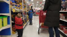 This is one of my creeper photos! It tells the story of a mom buying her two kids some toys. The little boy in the red jacket, Johnny, has a birthday coming up soon. He is super excited and can't tear himself away from the shelf. Meanwhile, Johnny's mom is watching her other son, Cris (blue jacket), because he is known for being mischievous. She doesn't want him to walk out of the store without paying for something again.