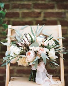 The bride's soft clutch of roses and dahlias was accented with leafy eucalyptus and olive branches, and burgundy agonis.