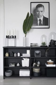 Black shelves in the sitting room of a charming norwegian home in green, grey and cognac. Henriette Amlie Kalbekken / Designlykke.