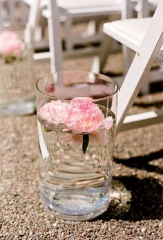 Clear glass cylinders with floating pink peonies beach wedding aisle decor