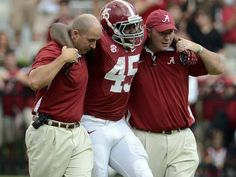 Alabama running back Jalston Fowler gets helped off the field by trainers after injuring his knee against Western Kentucky.