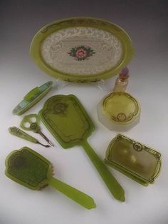 "Apple green ""Bakelite like"" Victorian vanity items to include a tray, handheld mirror, brush, cosmetic boxes, nail scissors and a nail buffer."