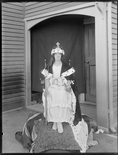 A woman, unidentified, dressed in fancy dress as a queen, sitting on a makeshift throne, outside an entrance to a wooden [hall?] building, possibly Christchurch district