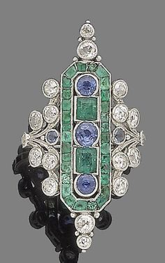 An Art Deco emerald, sapphire & diamond dress ring. The elongated octagonal cartouche, collet-set with a line of alternating circular-cut sapphires & rectangular-cut emeralds, within a border of calibré & circular-cut emeralds, accented by cushion-shaped diamond finials, between similarly-shaped diamond & circular-cut sapphire scrollwork shoulders, diamonds approx 1.05 cts total.