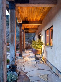 rough beams and stone patio - strength/solidity. Roof creates a transitionary feel between house and yard