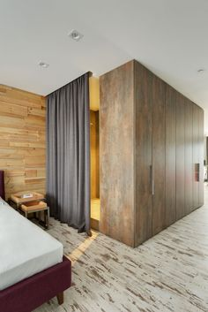 Apartment Aged Metal Panel Coated Bathroom Wall Charcoal Curtain Wood Piece Headboard Wall Modern Industrial Bedside Table Polished Dark Brown Wooden Bed White Sheet Mattress Unrefined Laminate Floor Industrial Loft Bedroom Industrial And Scruffy Stylish Bachelor's Apartment