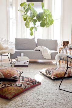 fiddle leaf fig + kilim floor pillows + white rug + bertoia diamond chairs. via apartment34.