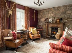 The living room of the flat features a stone wall, velvet curtains and leather arm chairs.