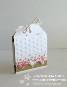 Amy's adorable Ghirardelli holder uses the Angled Tag Topper Punch with Language of Love, Little Labels, Adorning Accents embossing folder, Watercolor Wonder Washi Tape, & more. All supplies from Stampin' Up! Directions provided.