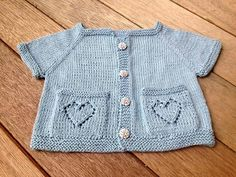 "A seamless baby cardigan, worked from the neck down. Two lacy hearts adorn the pockets. A surprise heart can be found at the nape of the neck.To Fit Size: 0-3, (6-12, 18-24) months Approximate Chest: 17 ¼"", (19 ½, 21 ¼) Length: 8"", (9, 10)Materials 2, (2, 3)—50G balls of Brown Sheep Cotton Fine (222 yds each), in color Nymph - US size 2-24"" circular and double points - stitch markers, 4 in one color and 2 in another - scrap yarn - 4 buttons, each ½"" diameterGauge 8 sts, 10.5 rows= 1"" in ..."