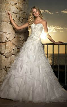 A-line Organza gown with ornately beaded bodice. The skirt is accented with ruffles. Stella York [Style 5671]