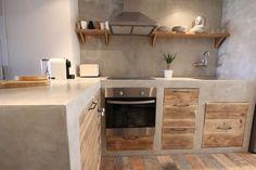 En este caso destaca el color claro del cemento en conjunción con la madera de los cajones: