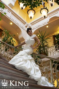 This bridal portrait was taken at Villa Antonia in Austin, Texas on a sprial staircase. The bride is wearing a dress by Geri A. Vela, at Alexia Gavela Bridal & Ceremonies. The dress is white, and while it has elements of a shealth dress, which runs very vertical it is stylish like a mermaid or trumpet wedding dress, which is a great dress for accentuate a curvy figure and a beautiful fit. Elegant, traditional and charming! Colors are white, yellow, canary, offwhite. Ruffles galore!